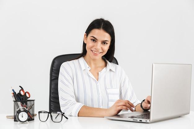 Zadowolony brunetka biznesmenka siedzi przy stole z papeterii i pracy na laptopie w biurze odizolowane na białej ścianie