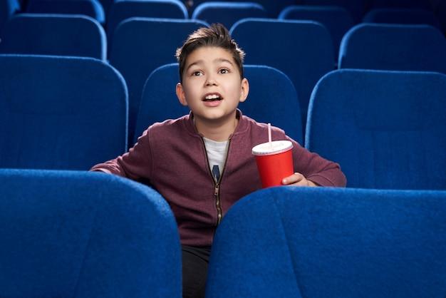Zadowolony chłopak ogląda ciekawy film w kinie