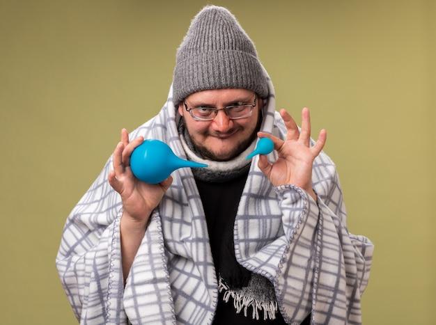 Zadowolony, chory mężczyzna w średnim wieku, ubrany w zimową czapkę i szalik owinięty w kratę, trzymający lewatywy izolowane na oliwkowozielonej ścianie