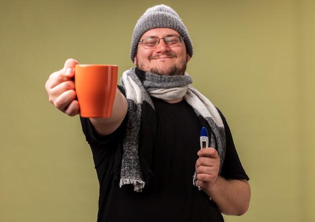 Zadowolony, chory mężczyzna w średnim wieku, ubrany w zimową czapkę i szalik, trzymający termometr i trzymający filiżankę herbaty odizolowaną na oliwkowozielonej ścianie