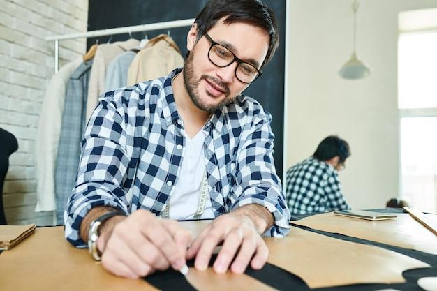 Zadowolony człowiek tworzący projekt odzieży