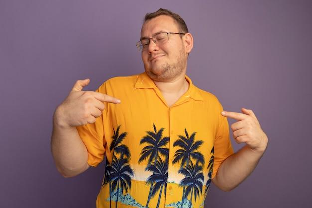 Zadowolony człowiek w okularach w pomarańczowej koszuli, wskazując na siebie szczęśliwy i wesoły stojący nad fioletową ścianą