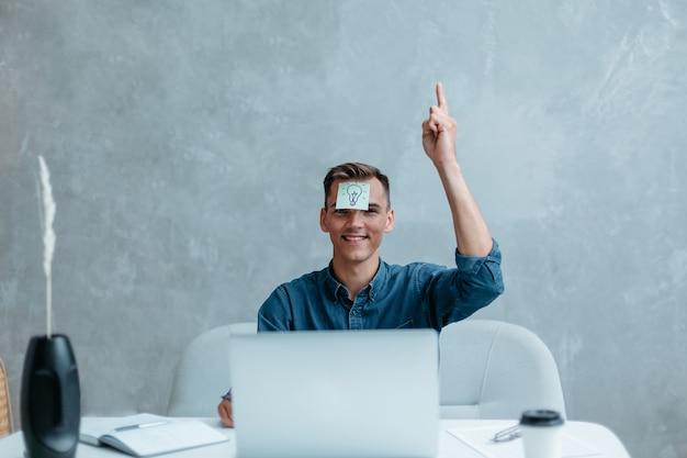 Zadowolony człowiek z podniesioną ręką myśli o dobrym pomysłem twórczym
