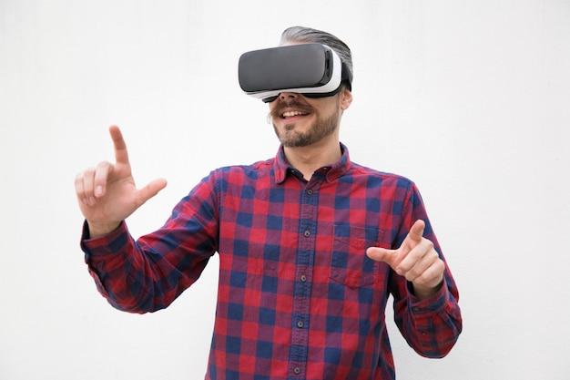 Zadowolony człowiek za pomocą zestawu słuchawkowego wirtualnej rzeczywistości