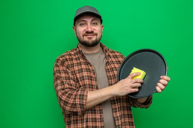 Zadowolony czystszy człowiek czyszczący naczynia za pomocą gąbki