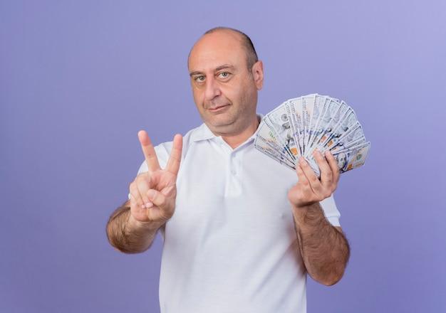 Zadowolony dojrzały biznesmen posiadający pieniądze i robiący znak pokoju