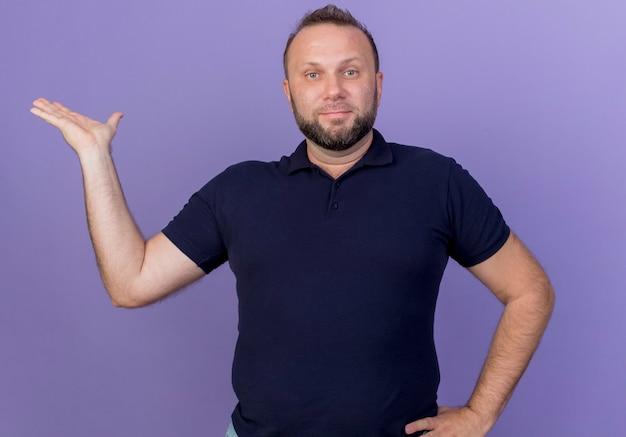 Zadowolony dorosły człowiek słowiański patrząc, trzymając rękę na talii i pokazując pustą dłoń na białym tle