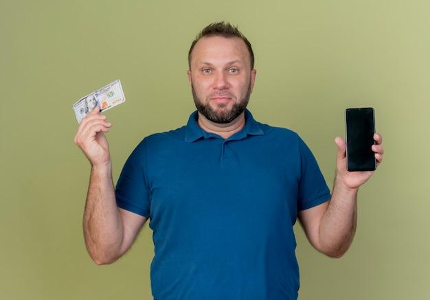 Zadowolony dorosły człowiek słowiański pokazując telefon komórkowy i pieniądze