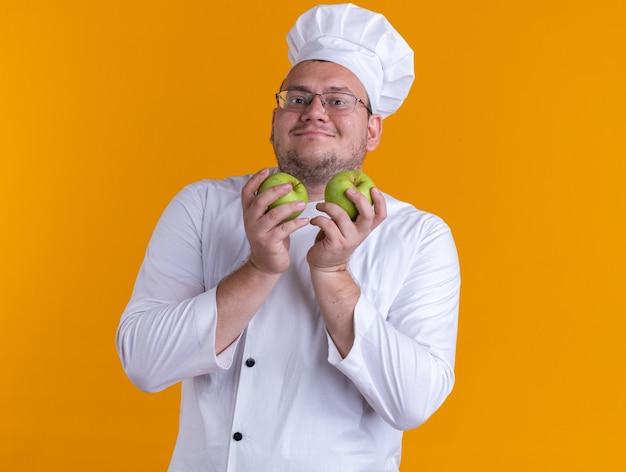 Zadowolony dorosły mężczyzna kucharz ubrany w mundur szefa kuchni i okulary trzymający jabłka patrzący na przód odizolowany na pomarańczowej ścianie