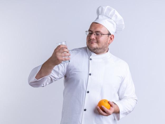 Zadowolony dorosły mężczyzna kucharz w mundurze szefa kuchni i okularach trzymających pomarańczę i szklankę wody, patrząc na szklankę wody odizolowaną na białej ścianie
