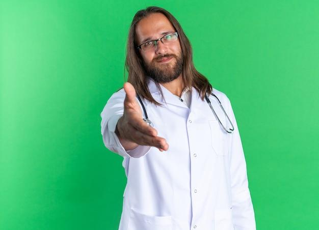 Zadowolony dorosły mężczyzna lekarz ubrany w szatę medyczną i stetoskop w okularach, patrząc na kamerę, wykonując gest powitania na zielonej ścianie z kopią przestrzeni
