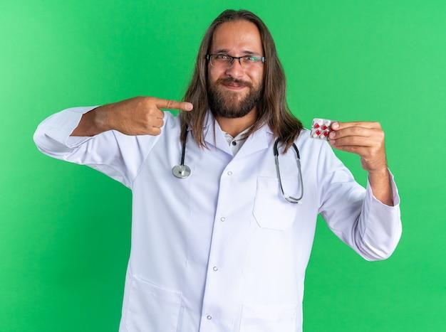 Zadowolony dorosły mężczyzna lekarz ubrany w szatę medyczną i stetoskop w okularach pokazujących i wskazujących na opakowanie kapsułek, patrząc na kamerę odizolowaną na zielonej ścianie