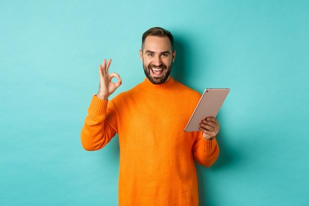 Zadowolony dorosły mężczyzna, uśmiechając się, używając cyfrowego tabletu i pokazując dobry znak, zatwierdza i zgadza się, stoi