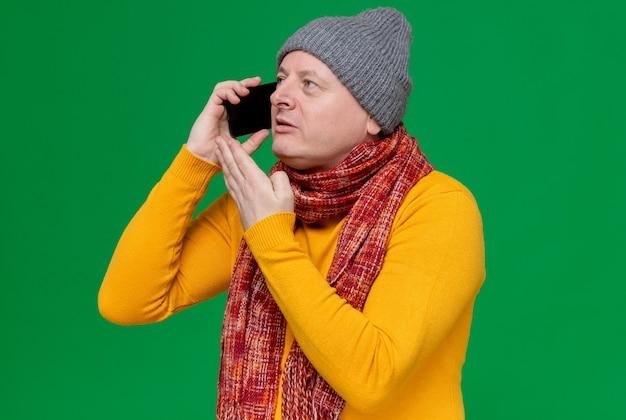 Zadowolony dorosły mężczyzna w czapce zimowej i szaliku na szyi rozmawia przez telefon, patrząc na bok