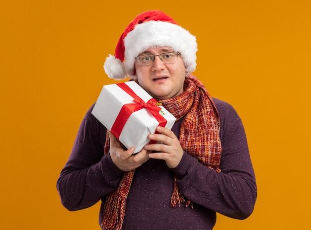 Zadowolony dorosły mężczyzna w okularach i santa hat trzyma pakiet prezentów odizolowany na pomarańczowej ścianie