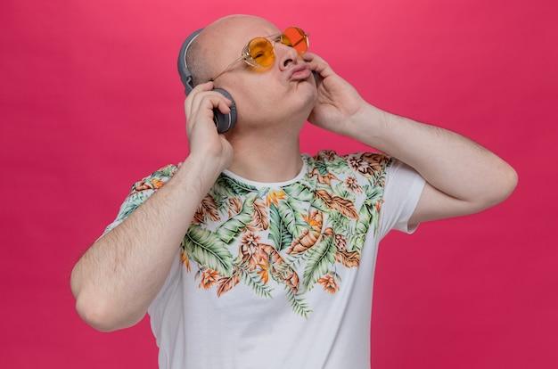 Zadowolony dorosły mężczyzna w okularach przeciwsłonecznych i na słuchawkach patrzący w górę