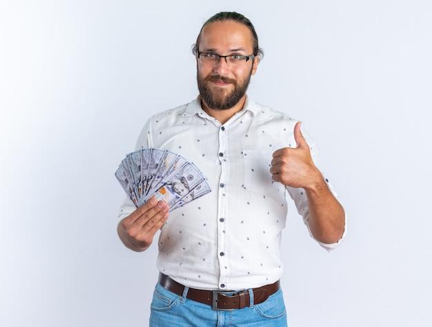 Zadowolony dorosły przystojny mężczyzna w okularach pokazujących pieniądze i kciuk w górę, patrząc na kamerę na białym tle na białej ścianie