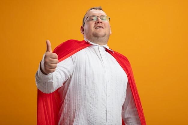 Zadowolony dorosły słowiański człowiek superbohatera w czerwonej pelerynie w okularach pokazujący kciuk w górę patrząc na kamerę odizolowaną na pomarańczowym tle z przestrzenią do kopiowania