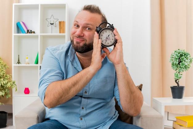 Zadowolony dorosły słowiański mężczyzna siedzi na fotelu, trzymając budzik blisko twarzy w zaprojektowanym salonie