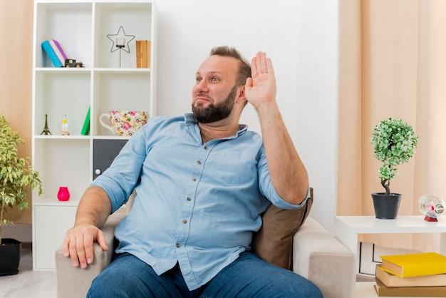 Zadowolony dorosły słowiański mężczyzna siedzi na fotelu z podniesioną ręką, patrząc z boku w salonie