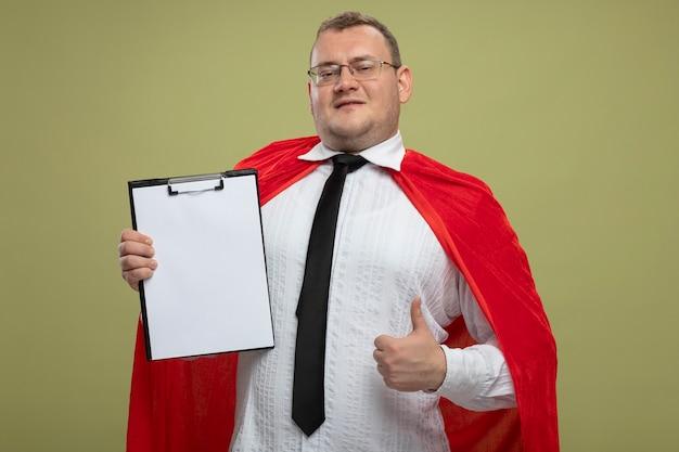 Zadowolony dorosły słowiański mężczyzna superbohatera w czerwonej pelerynie w okularach i krawacie, trzymając schowek, patrząc na kamerę, pokazując kciuk w górę na białym tle na oliwkowym tle