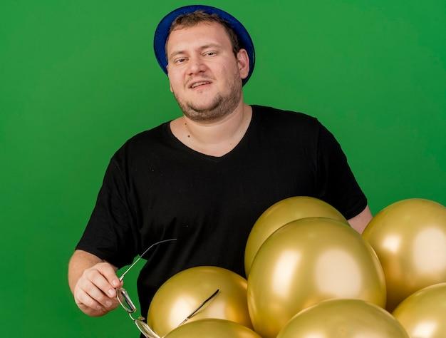 Zadowolony dorosły słowiański mężczyzna trzyma okulary optyczne w niebieskiej imprezowej czapce stojącej z balonami z helem
