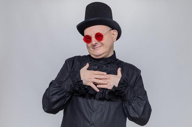 Zadowolony dorosły słowiański mężczyzna w cylindrze i okularach przeciwsłonecznych w czarnej gotyckiej koszuli kładzie ręce na jego klatce piersiowej