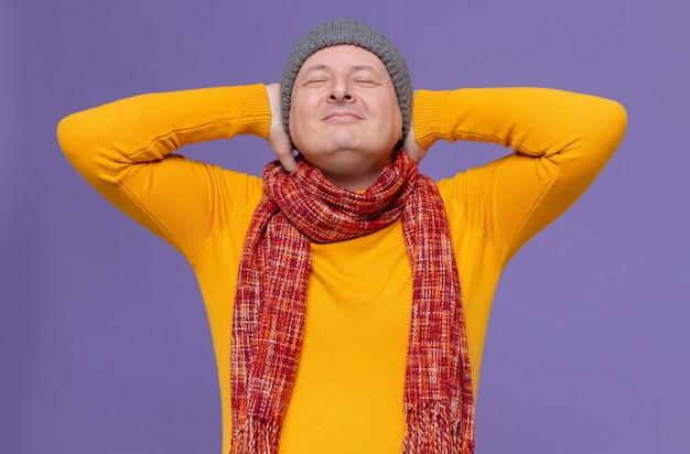 Zadowolony dorosły słowiański mężczyzna w czapce zimowej i szaliku na szyi, kładąc ręce na głowie