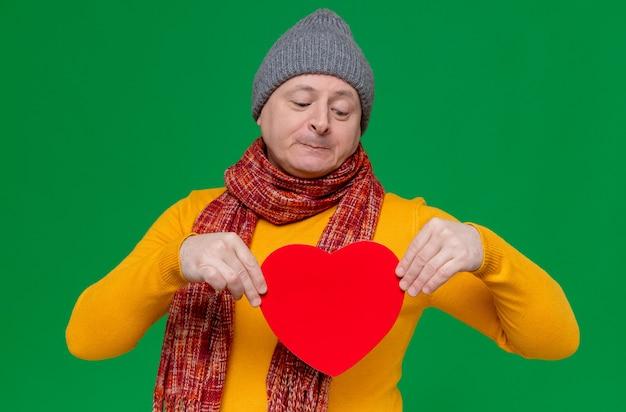 Zadowolony dorosły słowiański mężczyzna w czapce zimowej i szaliku na szyi, trzymający i patrzący na kształt czerwonego serca
