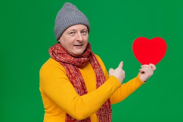 Zadowolony dorosły słowiański mężczyzna w czapce zimowej i szaliku na szyi, trzymający i wskazujący na kształt czerwonego serca