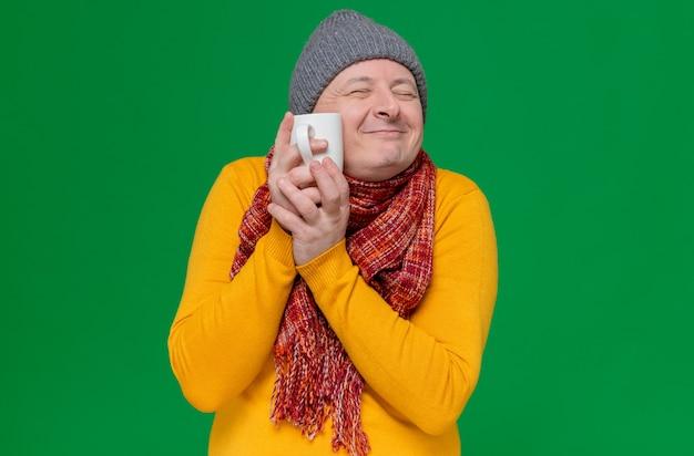 Zadowolony dorosły słowiański mężczyzna w czapce zimowej i szaliku na szyi, trzymający kubek blisko twarzy