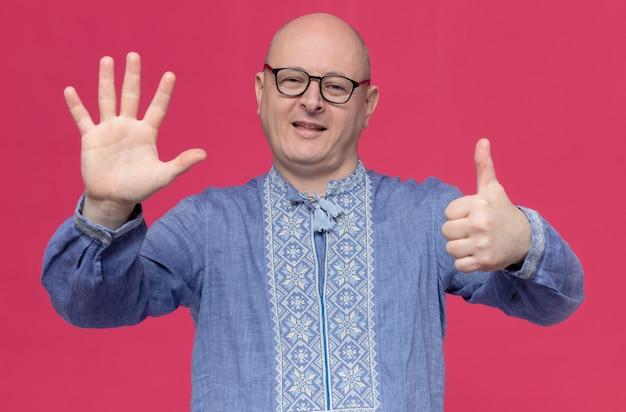 Zadowolony dorosły słowiański mężczyzna w niebieskiej koszuli w okularach optycznych, gestykulujący sześcioma palcami
