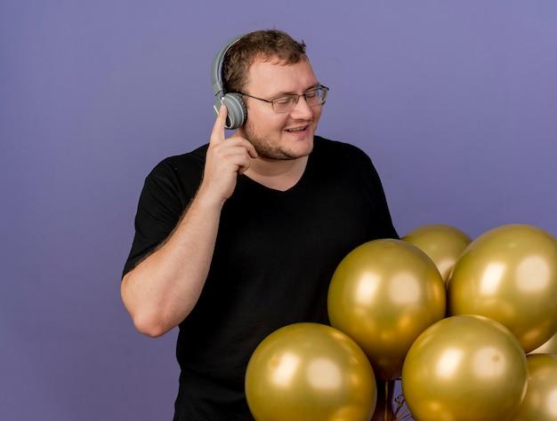 Zadowolony dorosły słowiański mężczyzna w okularach optycznych i na słuchawkach stoi z zamkniętymi oczami obok balonów z helem