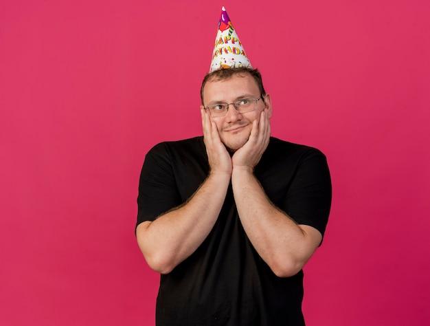 Zadowolony dorosły słowiański mężczyzna w okularach optycznych w czapce urodzinowej kładzie ręce na twarzy