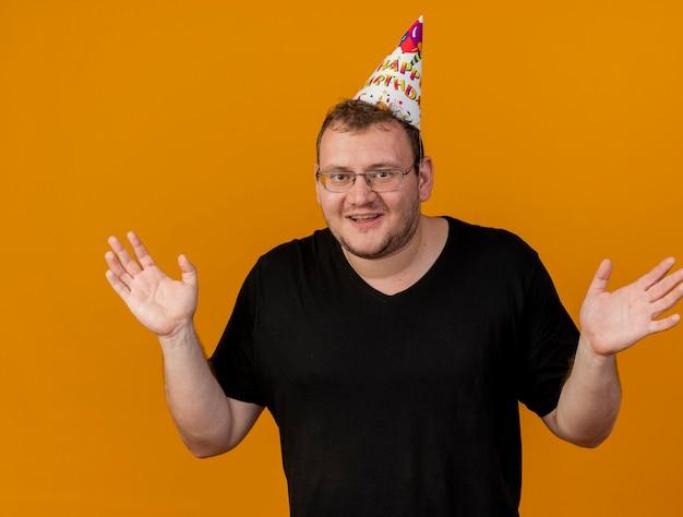 Zadowolony dorosły słowiański mężczyzna w okularach optycznych w czapce urodzinowej stoi z podniesionymi rękami