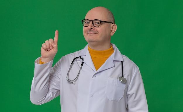 Zadowolony dorosły słowiański mężczyzna w okularach optycznych w mundurze lekarza ze stetoskopem skierowanym w górę