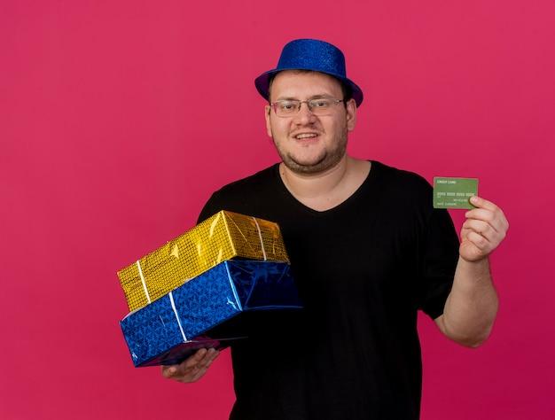 Zadowolony dorosły słowiański mężczyzna w okularach optycznych w niebieskim kapeluszu imprezowym trzyma pudełka na prezenty i kartę kredytową