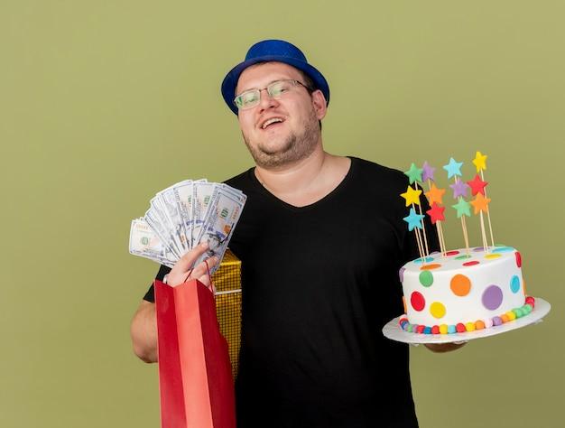 Zadowolony dorosły słowiański mężczyzna w okularach optycznych w niebieskim kapeluszu imprezowym trzyma pudełko z pieniędzmi papierową torbę na zakupy i tort urodzinowy