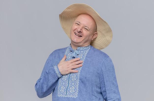 Zadowolony dorosły słowiański mężczyzna w słomkowym kapeluszu i niebieskiej koszuli kładzie rękę na jego klatce piersiowej i