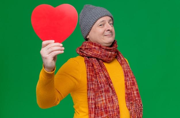 Zadowolony dorosły słowiański mężczyzna w zimowej czapce i szaliku na szyi, trzymający kształt czerwonego serca i patrzący z przodu