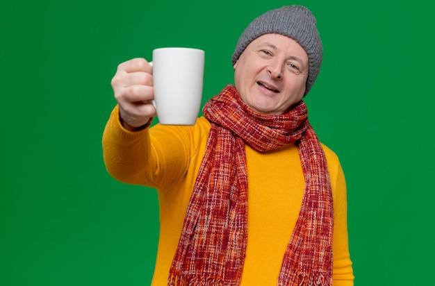 Zadowolony dorosły słowiański mężczyzna w zimowej czapce i szaliku na szyi, wyciągając filiżankę