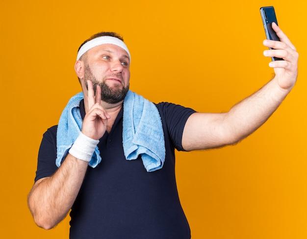 Zadowolony dorosły słowiański sportowy mężczyzna z ręcznikiem na szyi, z opaską na głowę i opaskami na nadgarstek, biorący selfie, gestykulujący znak zwycięstwa na pomarańczowej ścianie z miejscem na kopię