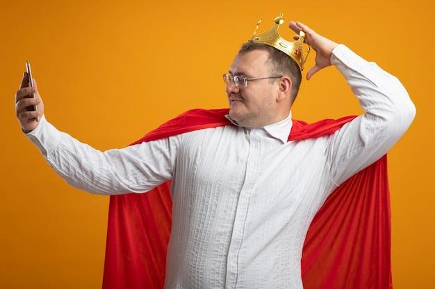 Zadowolony dorosły słowiański superbohater w czerwonej pelerynie w okularach i koronie dotykając korony, biorąc selfie na pomarańczowym tle