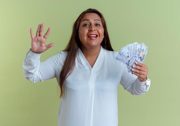 Zadowolony dorywczo kaukaski kobieta w średnim wieku trzyma pieniądze i pokazuje cztery