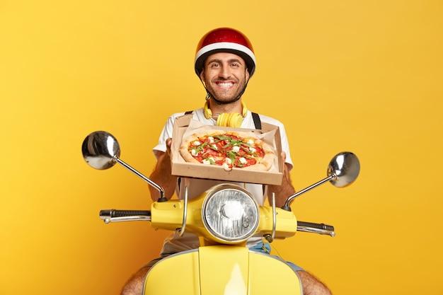 Zadowolony dostawca w kasku prowadzący żółtą hulajnogę, trzymając pudełko po pizzy