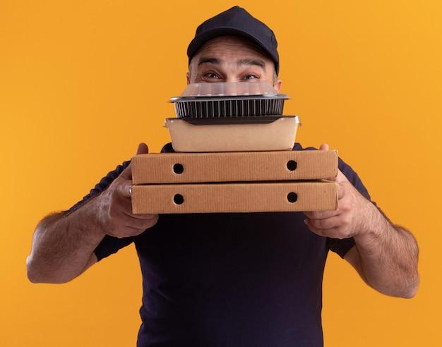 Zadowolony dostawczyni w średnim wieku w mundurze i zakrytej czapce twarzy z pojemnikiem na żywność na pudełkach po pizzy odizolowanych na żółtej ścianie