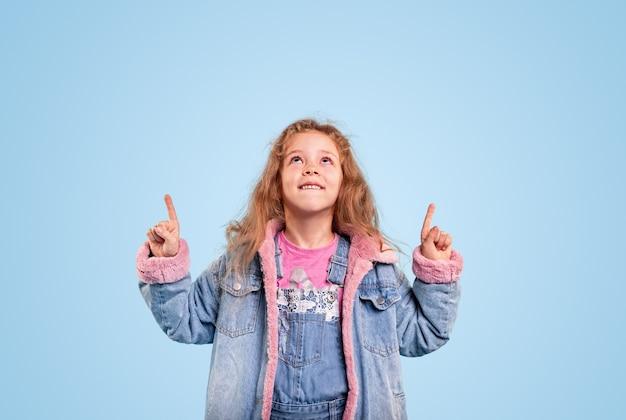 Zadowolony dzieciak w stylowej dżinsowej kurtce i kombinezonie skierowanym w górę