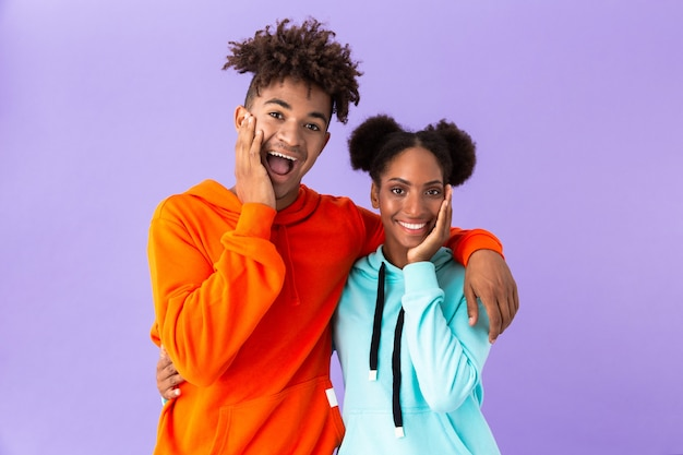 Zadowolony facet i dziewczyna stojąc razem i śmiejąc się, odizolowani na fioletowej ścianie