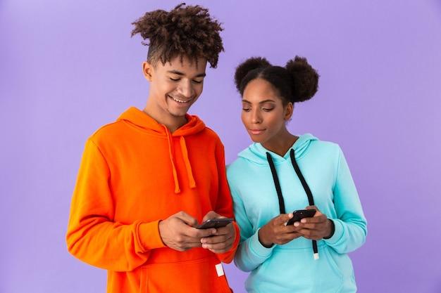 Zadowolony facet i dziewczyna za pomocą smartfonów, na białym tle nad fioletową ścianą