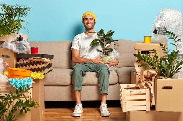 Zadowolony facet pozuje w pustym pokoju na kanapie